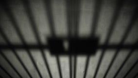 Sombra cerrada de la puerta de la celda de prisión en piso concreto oscuro de la cárcel almacen de video