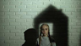 Sombra da casa na parede atrás da menina, das necessidades órfãos da criança em casa e da família video estoque