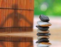 Sombra da ioga por pedras empilhadas no jardim imagens de stock