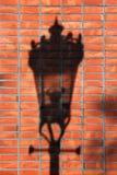 Sombra da lâmpada de rua em uma parede de tijolo vermelho Foto de Stock
