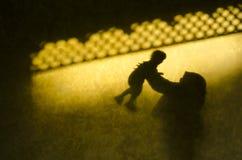 Sombra da mãe e da filha em uma parede amarela fotografia de stock