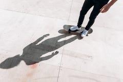 A sombra da posição do homem no skate no assoalho da corrediça em um parque do patim no dia ensolarado fora fotografia de stock royalty free