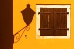 Sombra de la lámpara de calle en una pared amarilla Fotografía de archivo