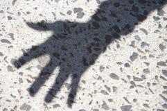 Sombra de la mano contra el pavimento Fotografía de archivo
