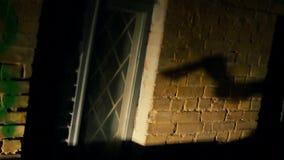 Sombra de la mano del maniaco con el hacha en la pared del edificio abandonado, película de terror almacen de video