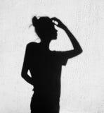 Sombra de la muchacha que toca un finger a su cabeza Fotografía de archivo libre de regalías