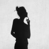Sombra de la muchacha que toca un finger a sus labios Imagen de archivo libre de regalías