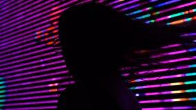 Sombra de la mujer joven en el fondo de la cartelera del anuncio, funcionamiento de la ciudad de la noche almacen de metraje de vídeo