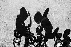 Sombra de los niños que montan una bicicleta en un pueblo de Bali Indonesia foto de archivo