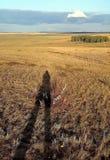A sombra de um homem em uma grama amarela Imagens de Stock