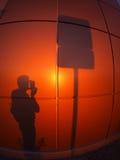 A sombra de um homem em uma parede vermelho-alaranjada imagem de stock