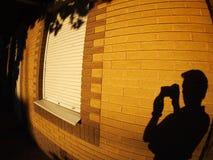 A sombra de um homem na parede iluminada de uma casa imagem de stock