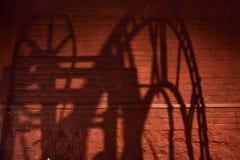 Sombra de um mecanismo do pulso de disparo com numerais romanos em uma parede de tijolo fotos de stock
