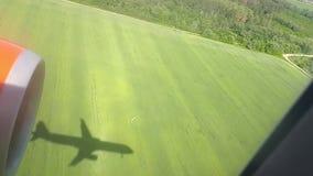 A sombra de um plano do voo na terra em um dia ensolarado Vista do indicador do avião Sombra do plano Voo sobre vídeos de arquivo