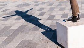 A sombra de uma jovem mulher com braços abertos projetou-se no pavimento Fotos de Stock Royalty Free