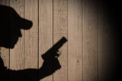 Sombra de un hombre con un arma Imagen de archivo