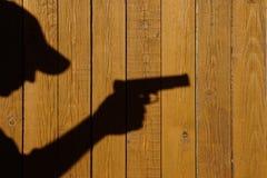 Sombra de un hombre con un arma en una cerca de madera Fotos de archivo