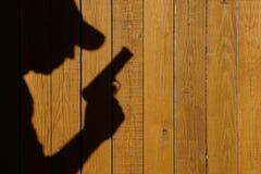 Sombra de un hombre con un arma en una cerca de madera Imagenes de archivo