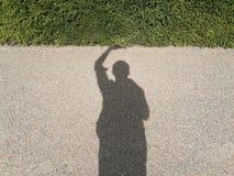 Sombra de un hombre que sostiene la hierba Imágenes de archivo libres de regalías