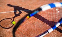 Sombra de un jugador de tenis en la acción en un campo de tenis Foto de archivo