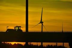 Sombra de un tractor y de un molino de viento de paso en una puesta del sol fantástica Imagenes de archivo