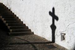 Sombra de una cruz con una escalera Fotos de archivo