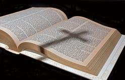 Sombra de una cruz en una biblia Fotos de archivo libres de regalías