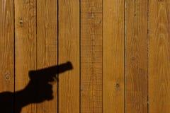 Sombra de una mano con un arma en una cerca de madera Fotografía de archivo libre de regalías