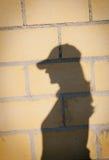 Sombra de una mujer con el sombrero en una pared Foto de archivo libre de regalías