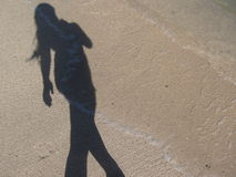 Sombra de una mujer que camina en la playa Imágenes de archivo libres de regalías