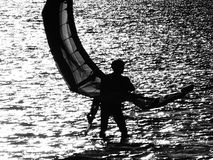 Sombra de una persona que practica surf de la cometa que lleva su vela B/W Fotografía de archivo libre de regalías