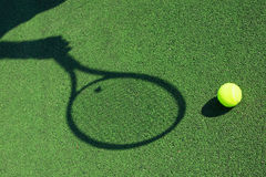 Sombra de una raqueta de tenis a disposición con una bola Fotos de archivo