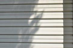 Sombra del árbol en la textura y el fondo blancos de la puerta de la lumbrera del hierro imagenes de archivo