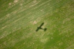 Sombra del aeroplano en campo verde Imagen de archivo