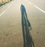 Sombra del ciclista en el camino de la pista de despeque Imagenes de archivo