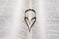 Sombra del corazón del bastidor del anillo en la biblia Fotografía de archivo libre de regalías