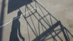 Sombra del deportista que gotea una bola y que la tira a través de la cesta, carrera almacen de metraje de vídeo
