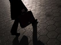 Sombra del hombre de negocios que recorre con la cartera Foto de archivo
