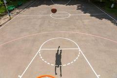 Sombra del hombre joven que hace el tiro en red del baloncesto Fotos de archivo libres de regalías