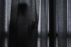 Sombra del ` s de la mujer que se coloca de ocultación detrás de la cortina Imagen de archivo libre de regalías