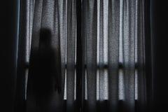 Sombra del ` s de la mujer que se coloca de ocultación detrás de la cortina Foto de archivo