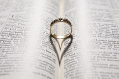 Sombra do coração da carcaça do anel na Bíblia Fotografia de Stock Royalty Free