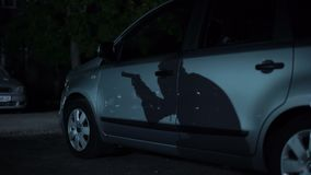Sombra do gângster com arma que anda na noite escura do estacionamento, área da cidade do alto-crime video estoque
