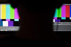 A sombra do homem que trabalha na frente dos colorbars monitora a estação de trabalho Fotografia de Stock Royalty Free