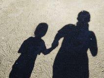 Sombra do pai e da filha na praia na praia, sombra dos povos Imagem de Stock