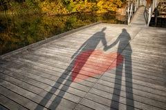Sombra dos pares que guardam as mãos com símbolo do coração Fotografia de Stock Royalty Free