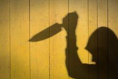 Sombra masculina de la mano con el cuchillo de cocina Foto de archivo