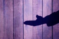 Sombra masculina en un fondo de madera, XXXL de la mano Fotos de archivo libres de regalías