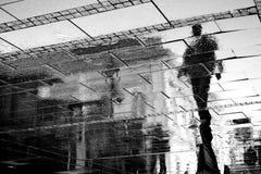 Sombra reflejada de un hombre en un día lluvioso Imagen de archivo libre de regalías