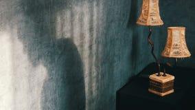 Sombra terrível corcunda na sala escura gótico ao lado de uma lâmpada do amarelo do vintage, comendo cookies e bebendo o chá de u video estoque